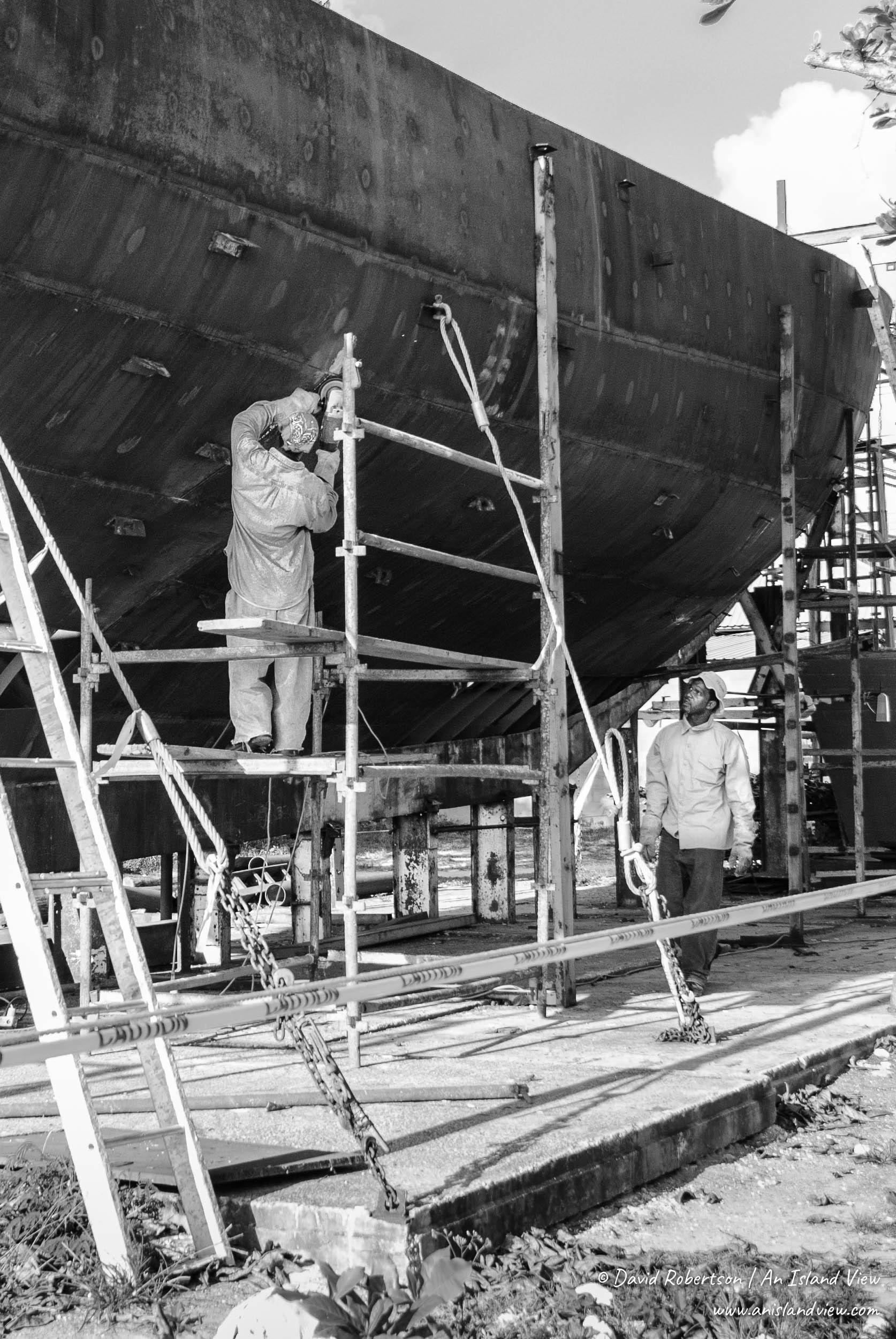 Man working on steel boat hull.