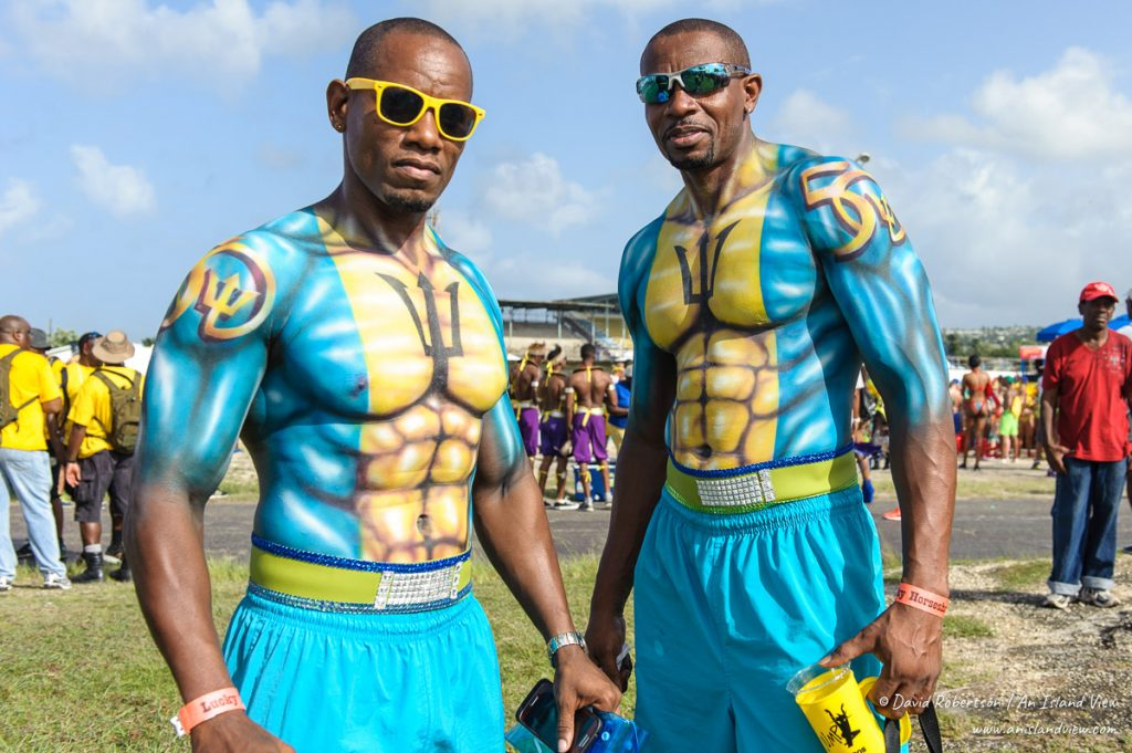 Two guys in Barbados flag body paint.